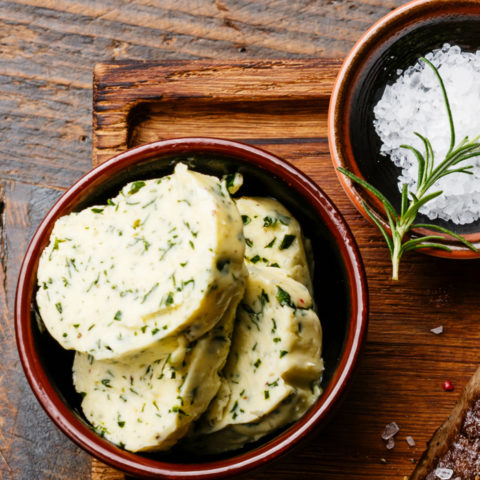 Sliced grilled steak Ribeye with herb butter on cutting board on wooden background