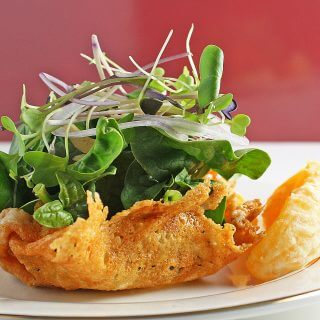 spinach and microgreen salad with fresh citrus dressing, served in parmigiano-reggiano cups