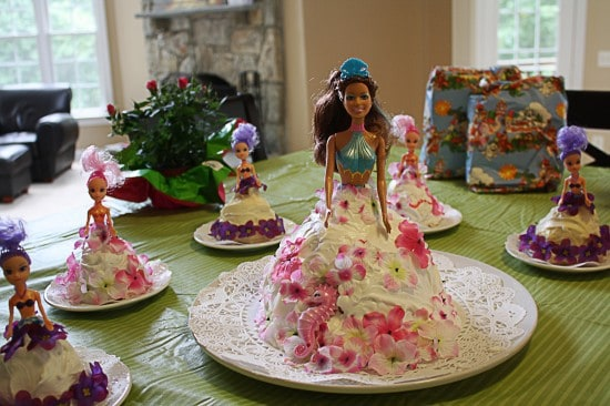 This easy and adorable Barbie Doll Cake uses a mermaid Barbie with tiny mermaid dolls for mini-cakes, too!
