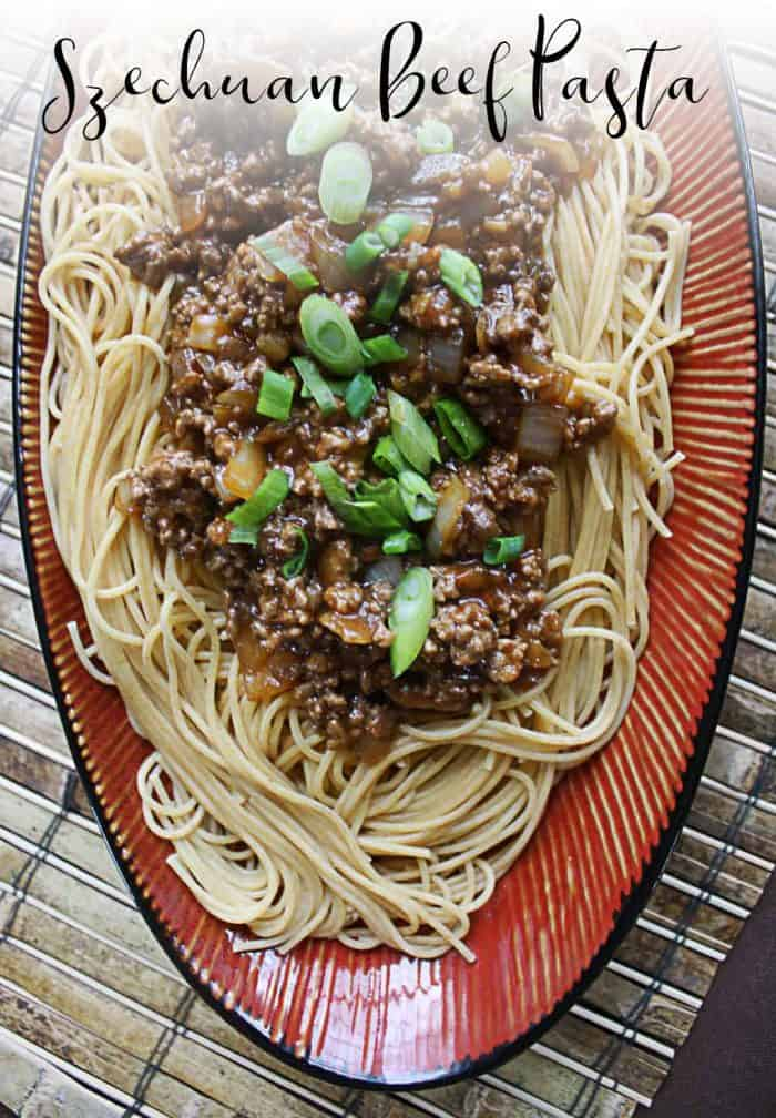 An oval Asian platter topped with Szechuan Beef and pasta, then topped with chopped green onions.
