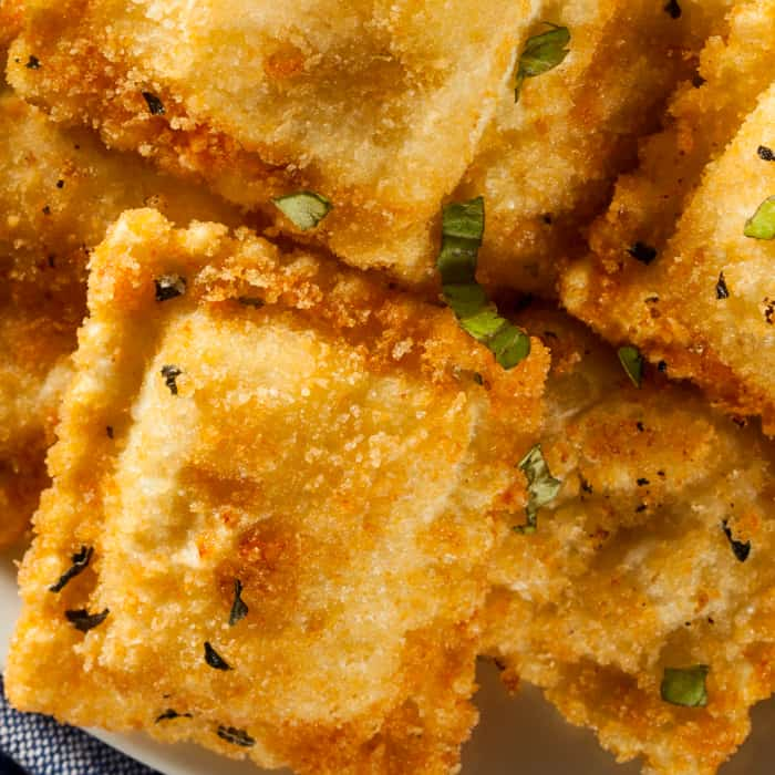 a closeup of fried ravioli sprinkled with chopped parsley