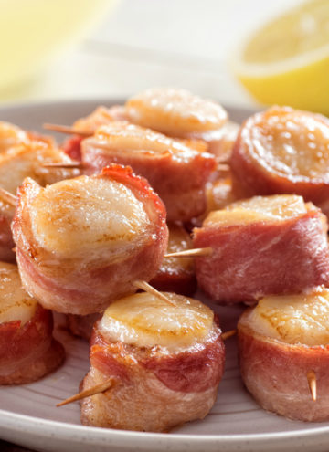 A plate of delicious bacon wrapped scallops with lemon.