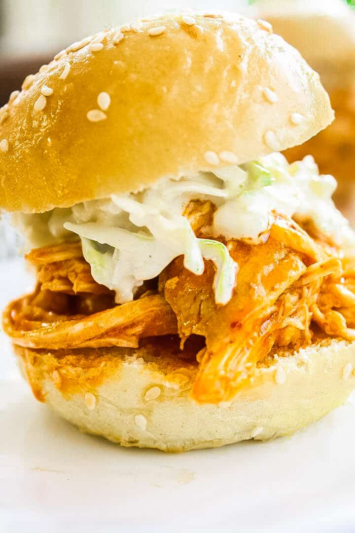 Buffalo Chicken Sliders topped with Blue Cheese Celery Slaw on a white plate