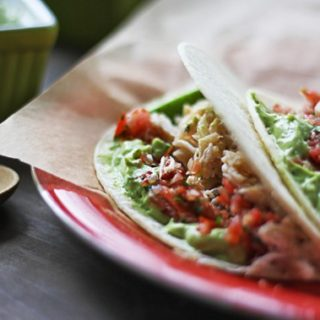 crab tacos with salsa and avocado sauce on a red plate