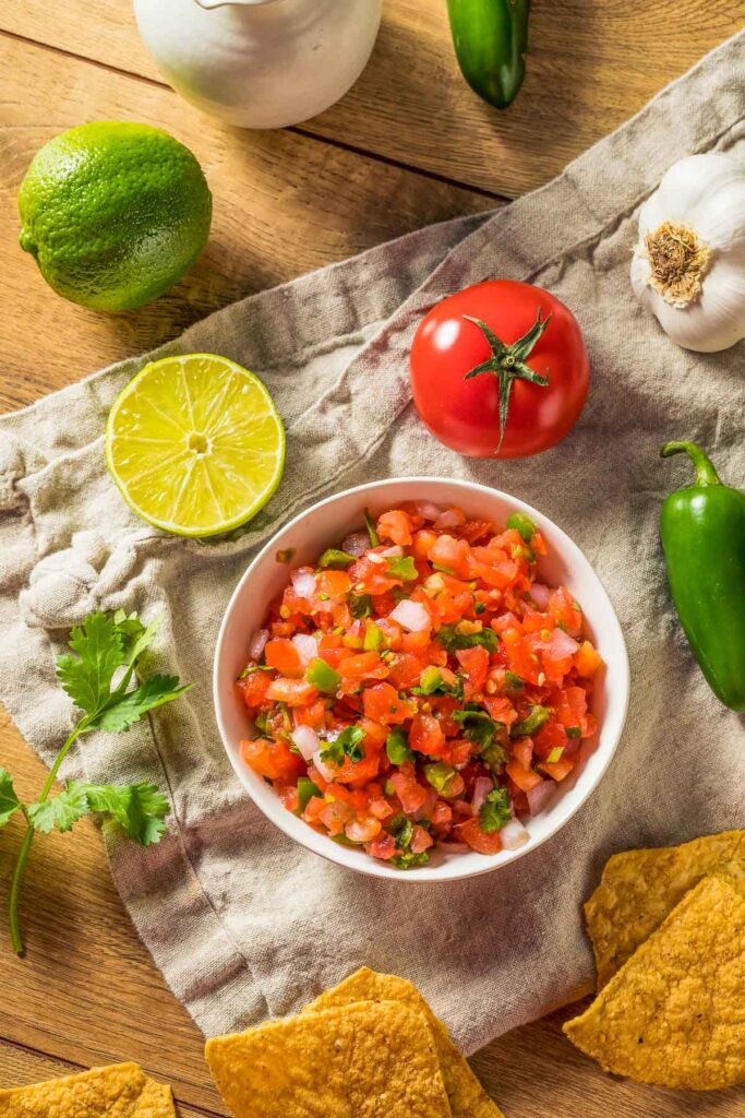 a bowl of pico de gallo with the ingredients around it on a table