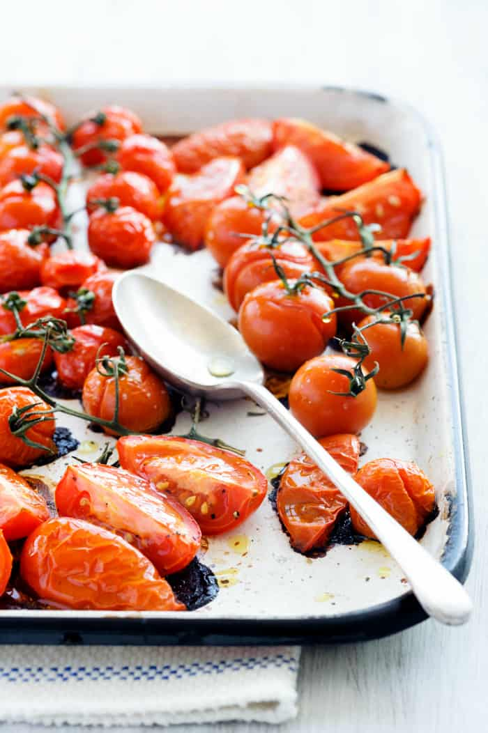 Baking tray filled with delicious juicy oven roasted tomatoes with large serving spoon