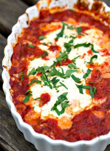 a white scalloped dish filled with goat cheese, marinara and fresh basil that's been baked