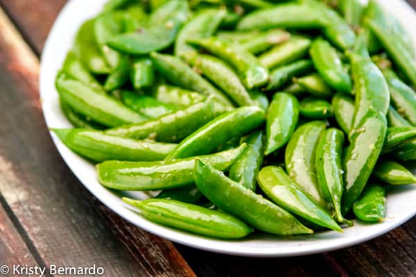 cooked snap peas on a white plate set on a wood table