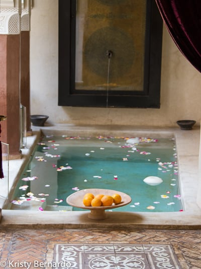 pool inside a Moroccan riad with rose petals