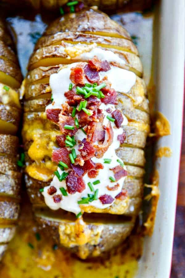 Gorgeous and easy baked potatoes loaded with chipotle sour cream, crispy bacon and chives! Hasselback potatoes are so easy to make with a buttery, soft inside, gooey cheese and all the fixins!