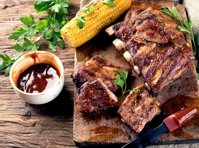 Pork ribs with corn on a wooden board.