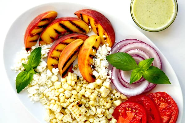 This Grilled Peach Salad with Basil Vinaigrette couldn't be easier to throw together and it's filled with flavor. The sweet peaches, fresh summer corn and salty feta are a to-die-for flavor combination!