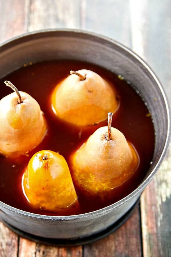 a pot filled with pears and syrup just before cooking and turned into healthy poached pears