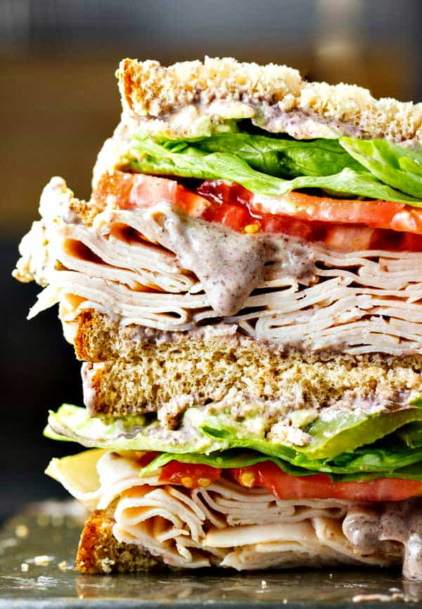A healthy turkey sandwich recipe! Piled high with turkey, lettuce, tomato, roasted anaheim peppers and a creamy black bean spread!
