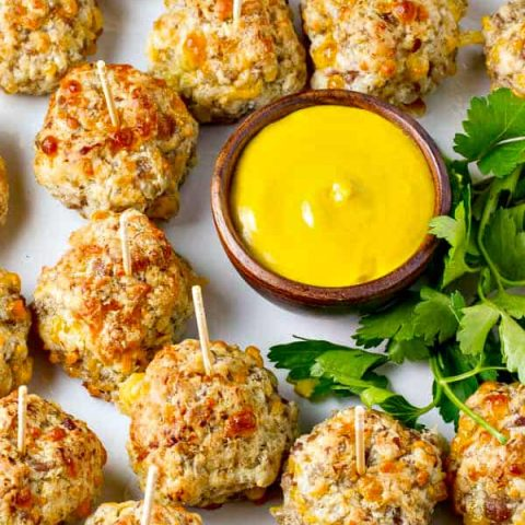 These super easy Bisquick Sausage Balls have just four ingredients, loads of sausage flavor and a cream cheese makes them moist and delish! Serve with mustard, your favorite dipping sauce or just on their own.