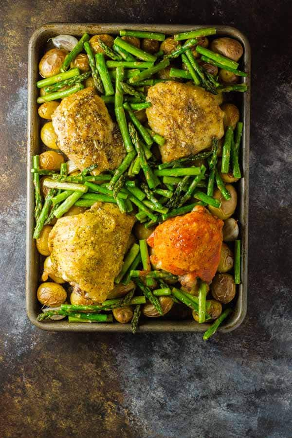 One-pan oven baked chicken thighs with potatoes and your side, plus a technique that easily allows for a different flavor chicken for each member of the family (and it only takes a minute)!