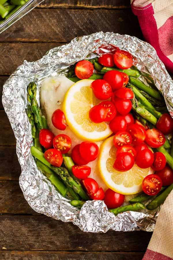 Here are FOUR simple ways to make Baked Tilapia in Foil! Toss 'em on the grill or in the oven - but NEVER have dishes to clean up! Healthy, delicious and every member of the family can choose their favorite flavor without much more effort for the chef!