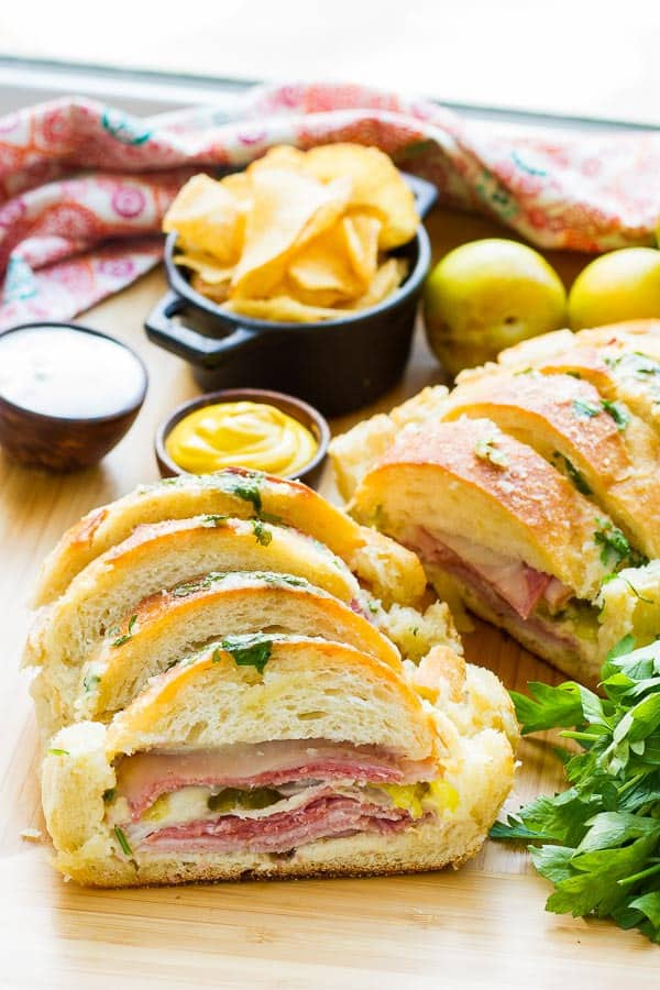 Why make individual sandwiches when you can make one BIG one that feeds everyone? This Garlic Bread Sandwich Loaf recipe has loads of goodies layered inside, then it's doused with a combination of melted butter, garlic, parmesan and parsley. It is AMAZING!! AND EASY!!