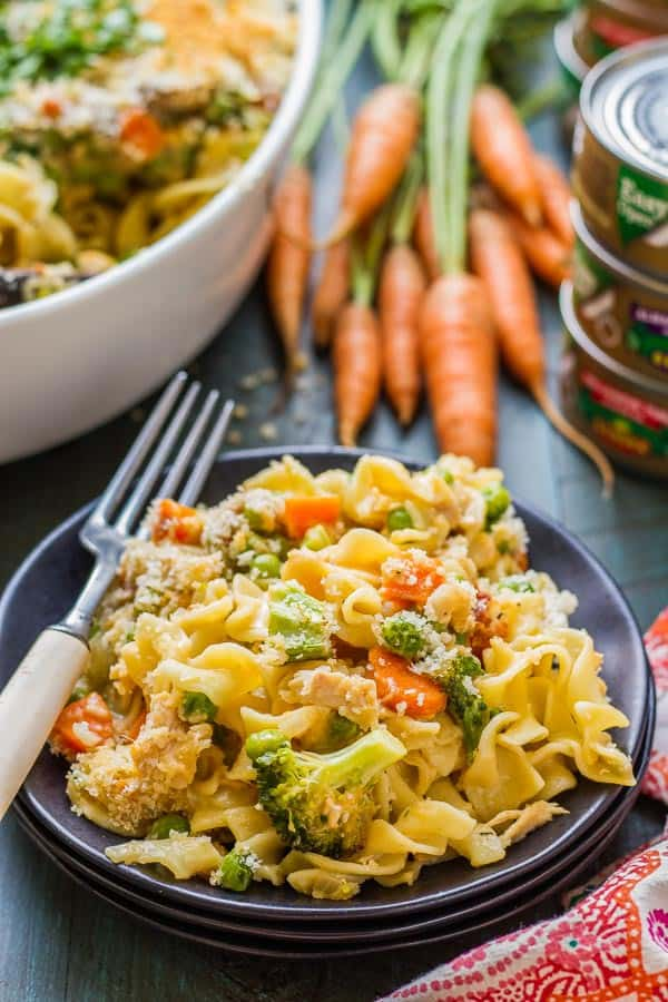 healthy tuna casserole on a black plate with carrots with tops in the background