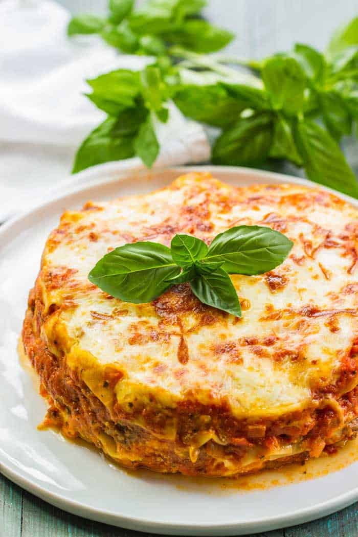 Instant pot lasagna on a white plate with fresh basil in the background