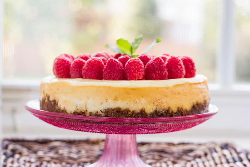 Lemon Instant Pot Cheesecake - the creamiest cheesecake we've made in our Instant Pot (or otherwise) yet! The gingerbread crust pairs perfectly with the delicate lemon flavor. Top it with fresh raspberries for a show-stopping dessert!
