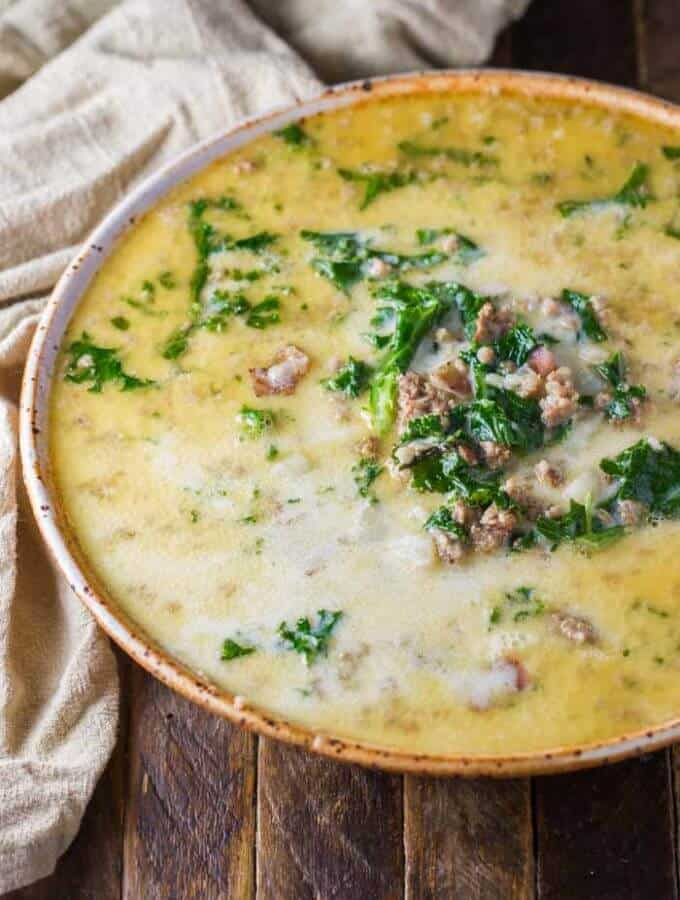 Instant Pot Zuppa Toscana Soup in a large bowl, sitting on a wood table with a beige towel.