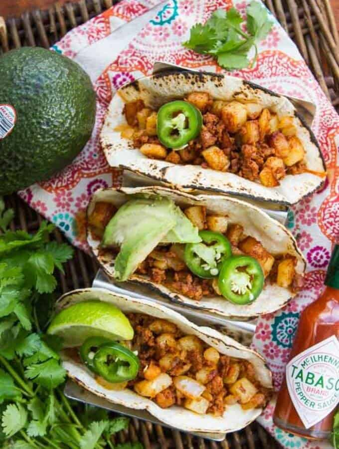 Three Chorizo & Potato Tacos next to an avocado and a bottle of TABASCO