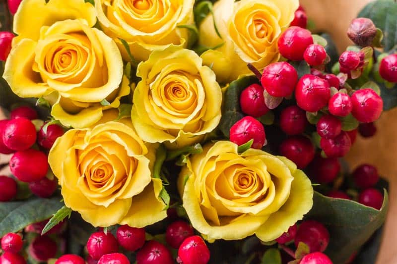 debi lilly floral bouquet with yellow roses and red berries