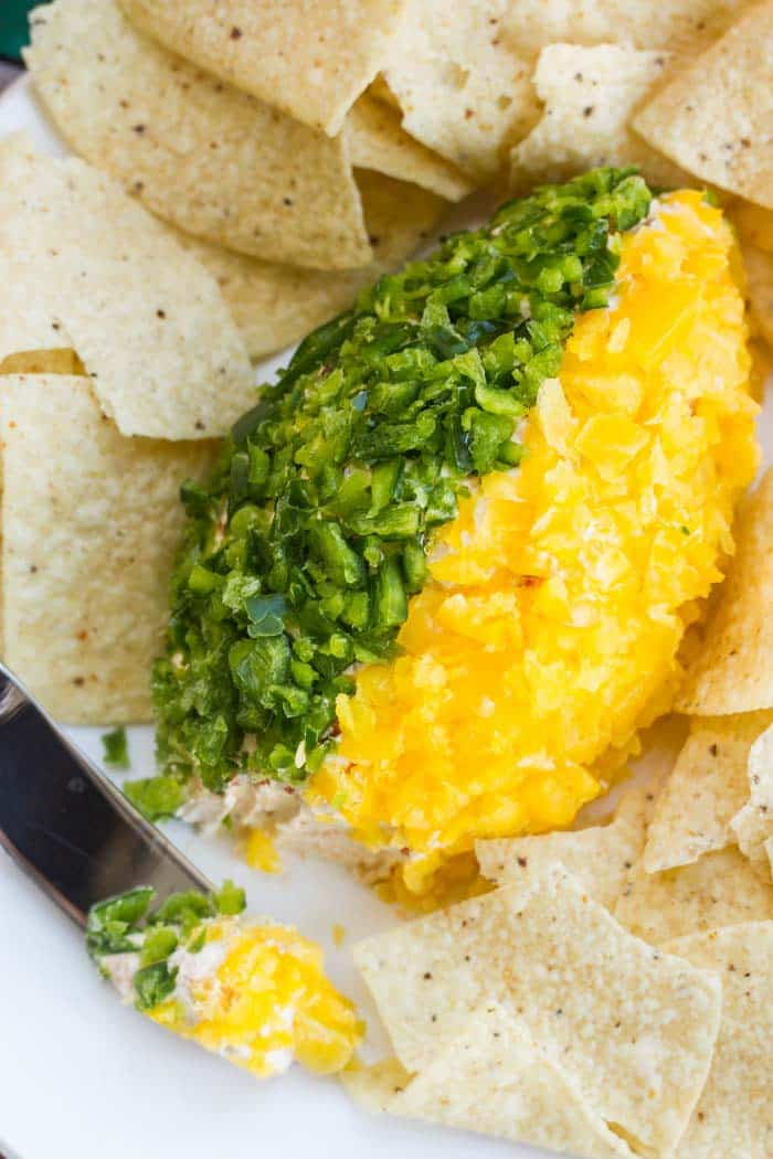 A salsa cheese ball appetizer with chopped poblanos and yellow bell peppers on the outside.