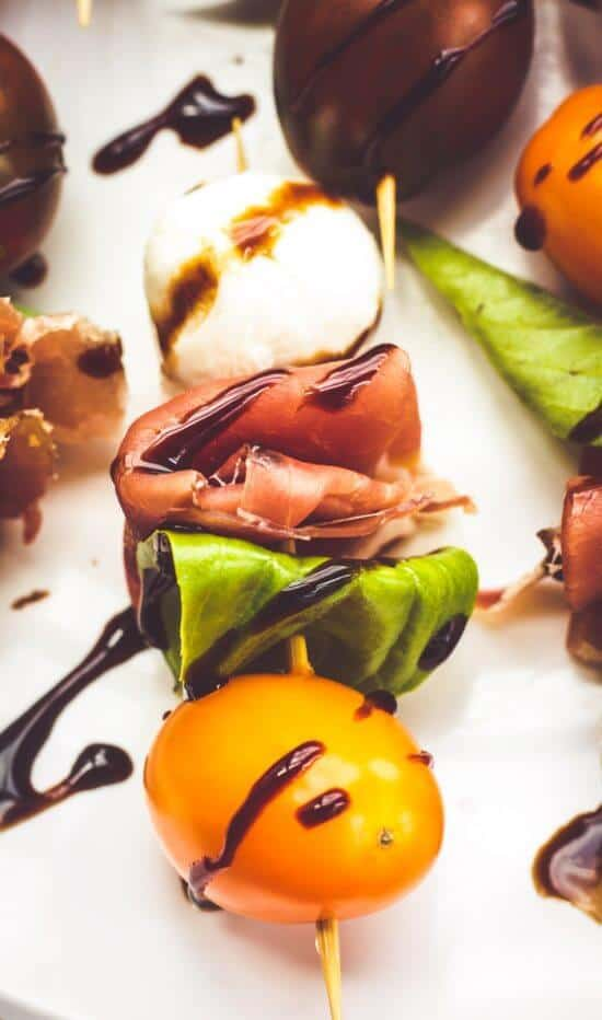 Ensalada Caprese Bites on a white plate, drizzled with balsamic vinegar