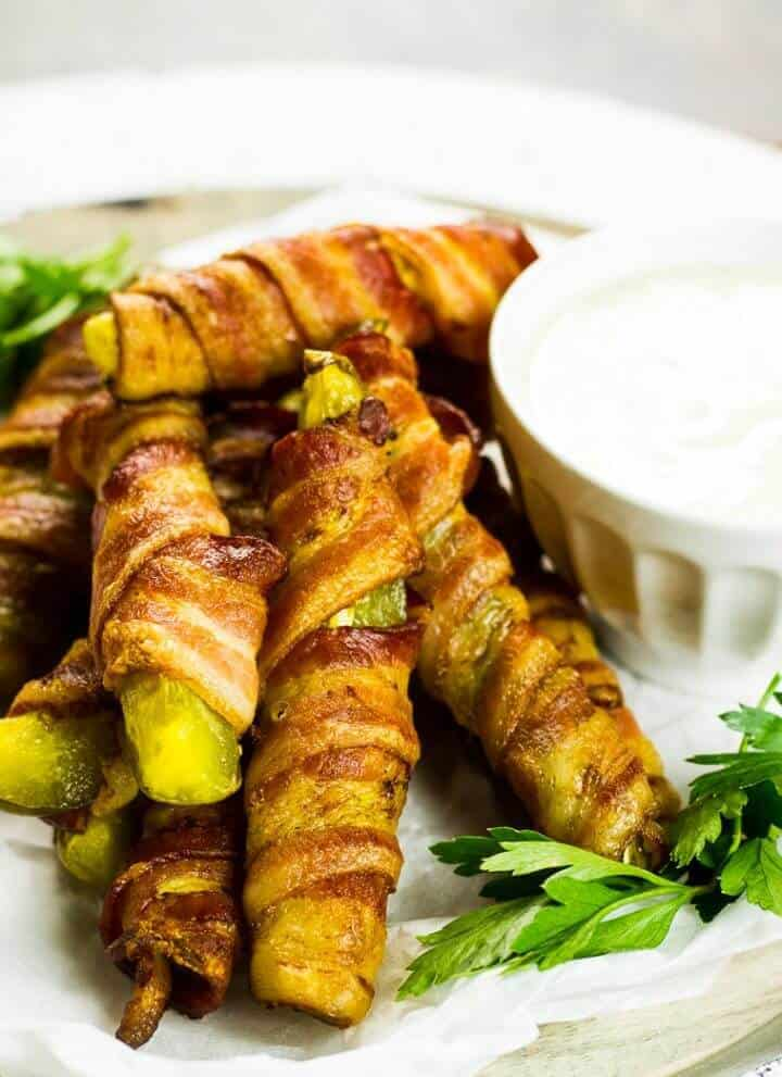 Bacon Wrapped Pickles on a plate with a bowl of dipping sauce.