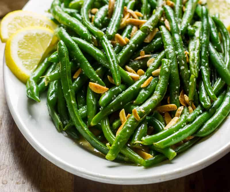 Green Beans Almondine on a white oval plate which sits on a wooden board with a rustic napkin next to it.