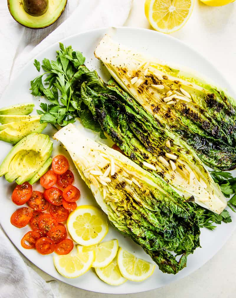 A keto salad on a white plate, made up with grilled romaine, sliced cherry tomatoes, thinly sliced avocado and halved lemon slices for a garnish.