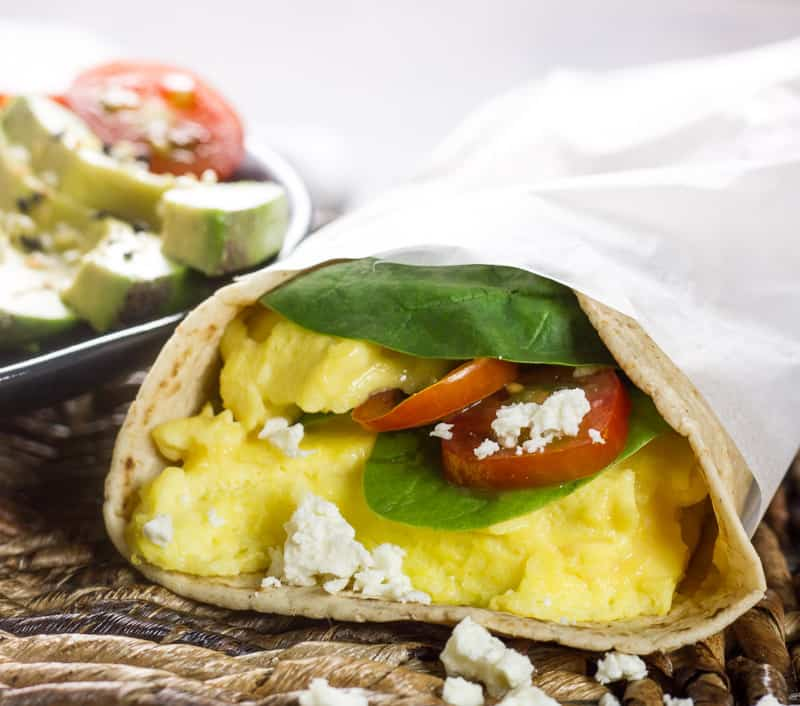 A spinach wrap that's been wrapped in parchment paper next to a plate of avocado and tomatoes