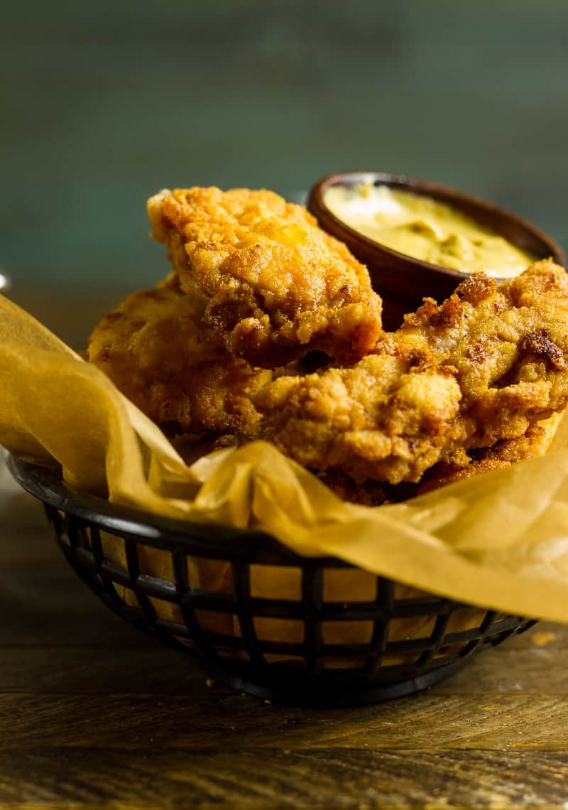Pickle Brined Keto Fried Chicken in a basket with brown parchment paper and a pickle spear and some garlic mustard aioli.