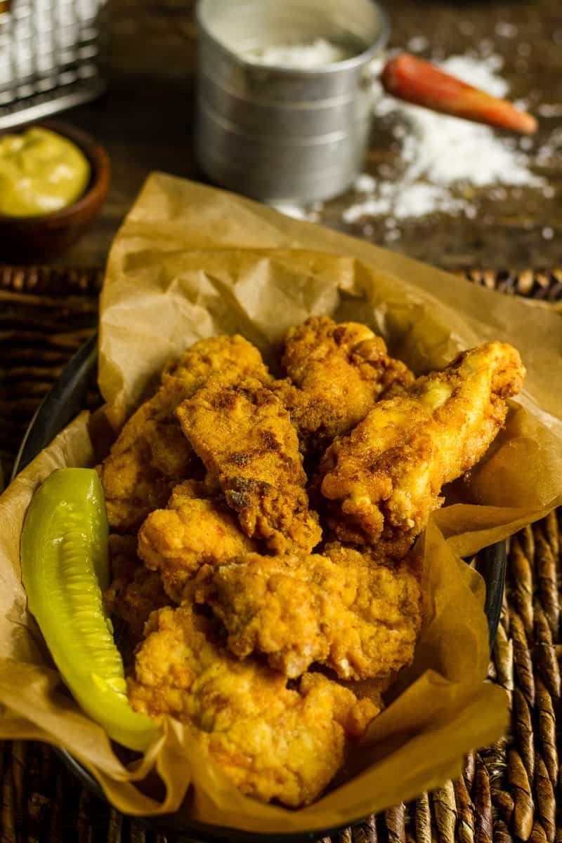 Pickle Brined Keto Fried Chicken in a basket with brown parchment paper and a pickle spear.