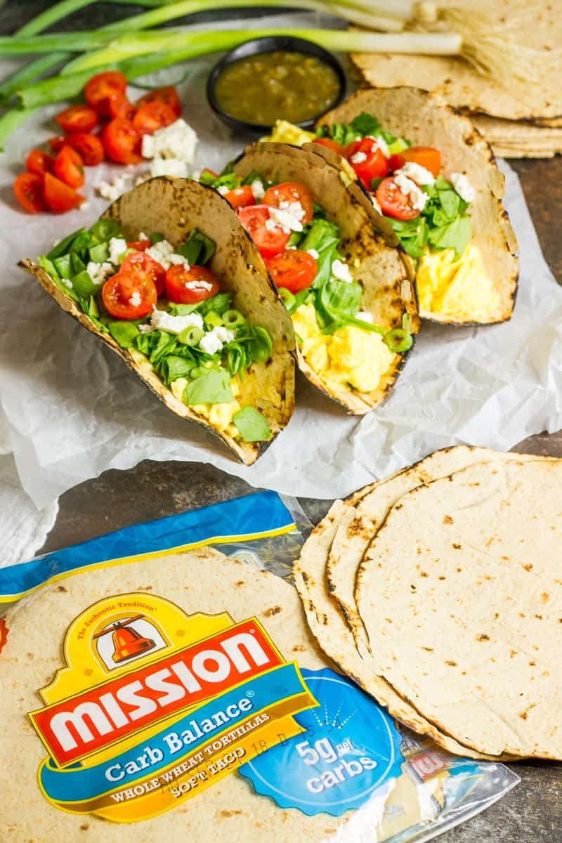 Spinach wraps next to a package of mission low carb tortillas on parchment paper