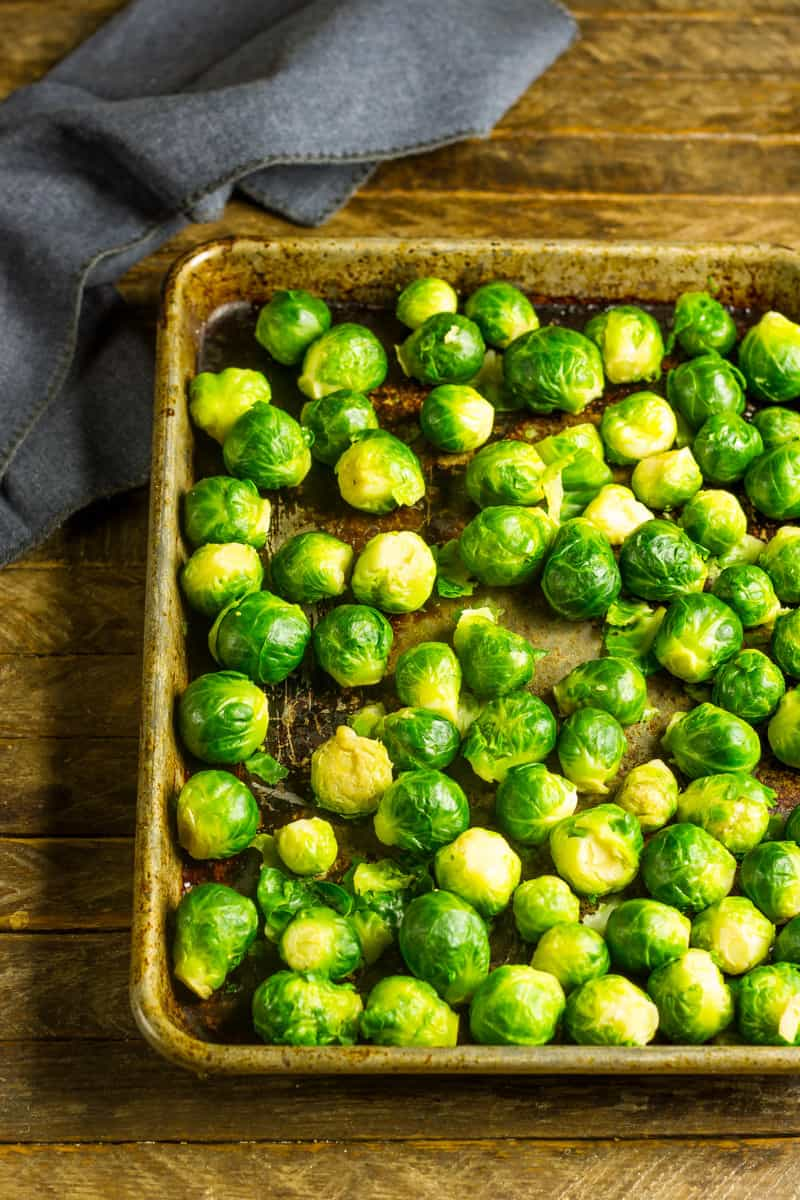 Smashed brussels sprouts on a sheet pan ready for the oven