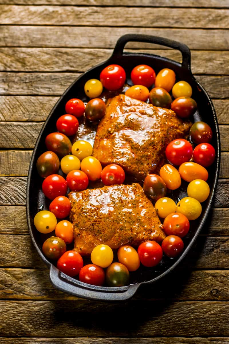 Blackened Salmon with Roasted Tomatoes ready for the oven on a cast iron pan