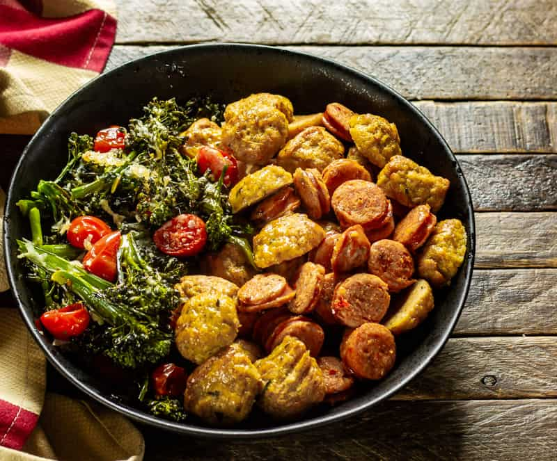 Sausage & Parmesan Broccoli Rabe Sheet Pan Dinner on a wooden table with a rustic napkin.