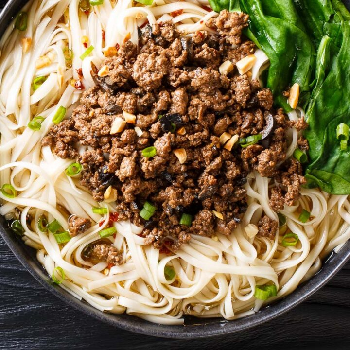 a plate of szechuan gourmet beef pasta on a black table with greens