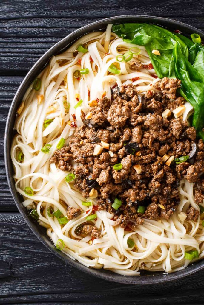 a plate of szechuan gourmet beef pasta on a black table with greens and chopped peanuts