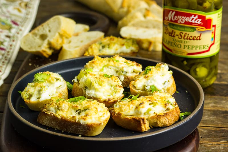 Jalapeno Relish Cheesy Toasts on a black plate that sits on a wooden table.