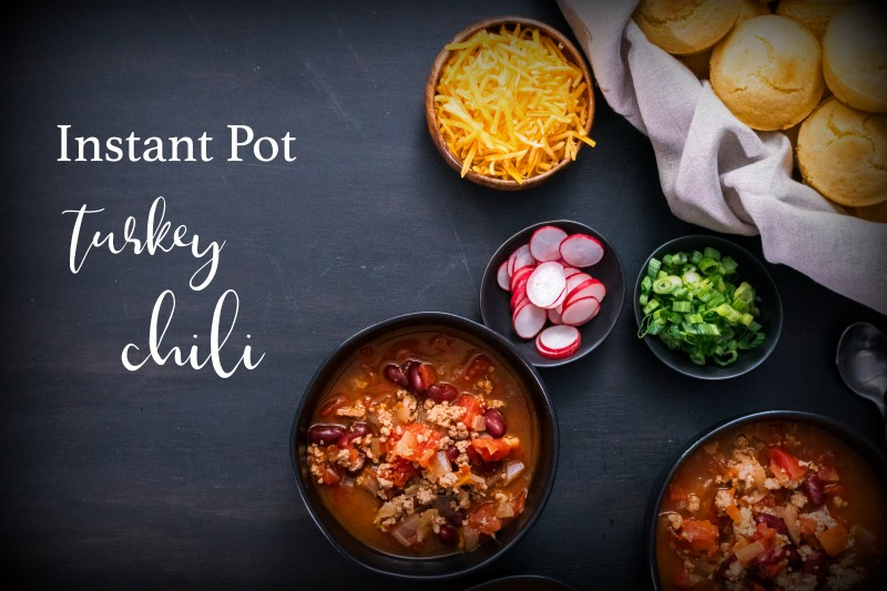 Instant Pot turkey chili garnished with fresh radishes, green onions and cheddar cheese.