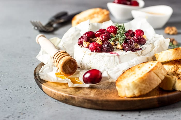 Baked Camembert with Cranberries and Walnuts on a wooden board with bread