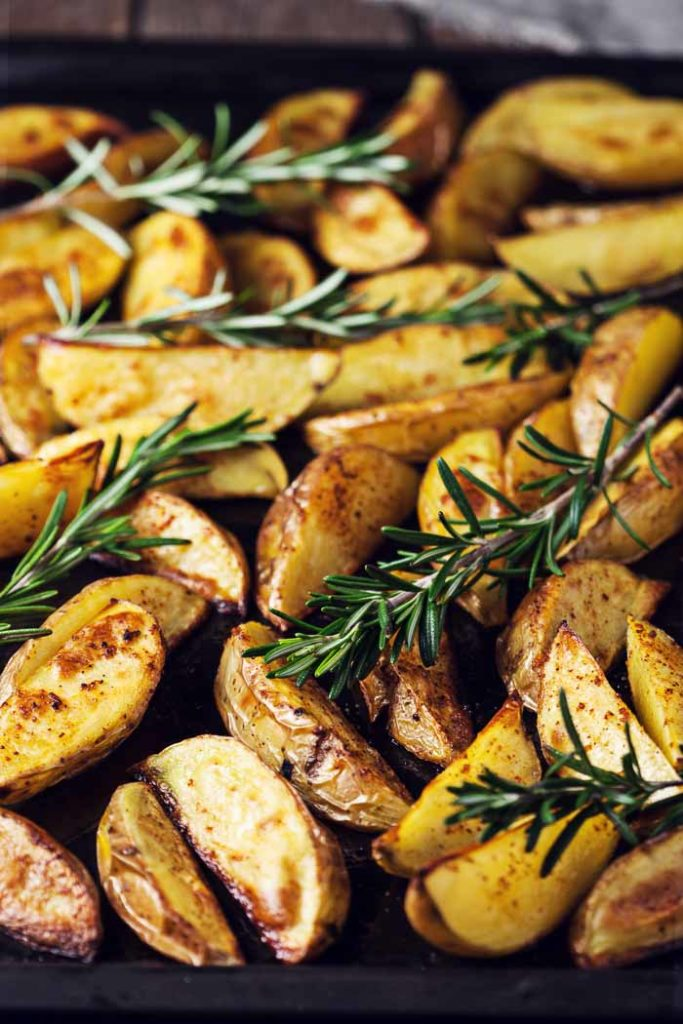 Baked Potato Wedges with fresh rosemary on a sheet pan