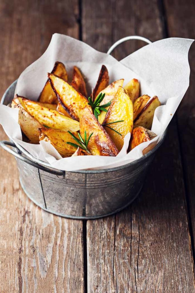 Baked Potato Wedges in a tin with parchment paper on a wooden table