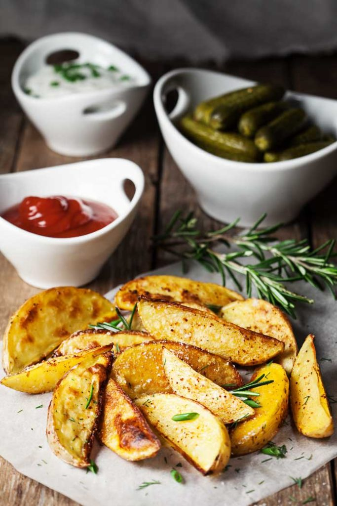 Baked potato wedges with dipping sauces and pickles on parchment paper on a wood table