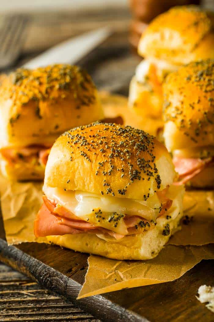 a platter of hot ham and cheese party sandwiches