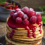 A stack of raspberry almond flour pancakes topped with fresh raspberries on a silver plate set on a wooden table